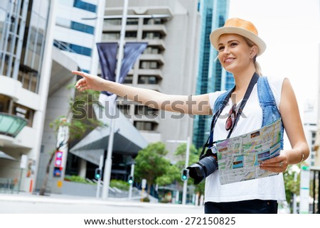 Female tourist calling for a taxi in the city - stock photo