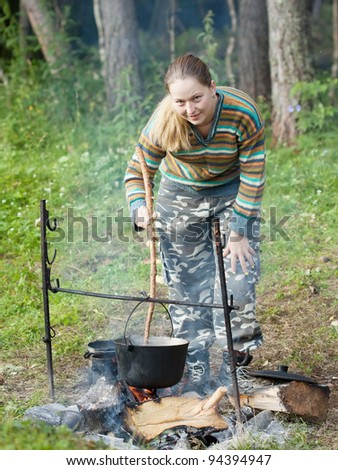 Female tourist cooking meal in kettle on fire - stock photo
