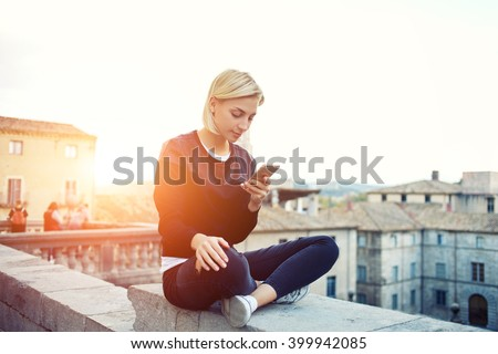 Female tourist is searching information on website via mobile phone about history this beautiful old town. Hipster girl is reading text message on cell telephone, while is sitting on a building roof - stock photo