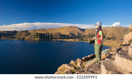 Female tourist looking at the majestic panoramic view from the top of the mountain in Copacabana, Titicaca Lake, among the most scenic travel destination in Bolivia. Travel adventures in the Americas. - stock photo