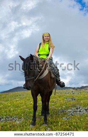 Female tourist on horseback at mountains - stock photo