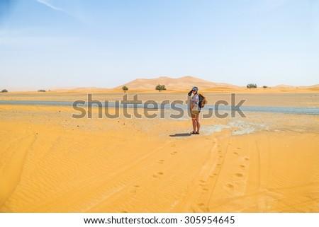 Female tourist on sand dunes in Merzouga, Morocco - stock photo