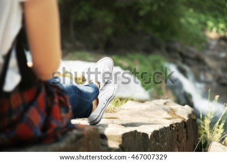 Female tourist sitting on stone beside the stream