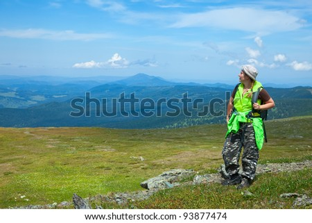 Female tourist standing on mountain pass and looking to  valley below - stock photo