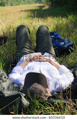 Female tourist taking nap in a field - stock photo