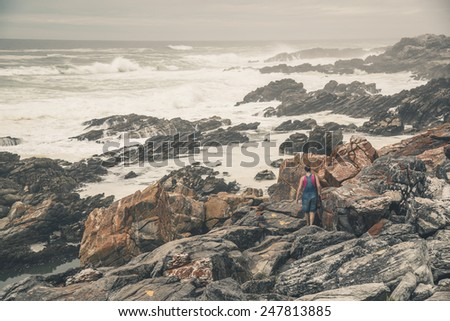 Female tourist walking along the wild coast of Tsitsikamma National Park. Eastern Cape. South Africa.