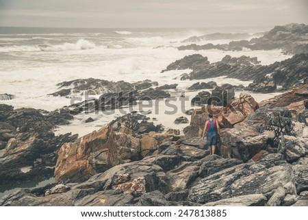 Female tourist walking along the wild coast of Tsitsikamma National Park. Eastern Cape. South Africa. - stock photo