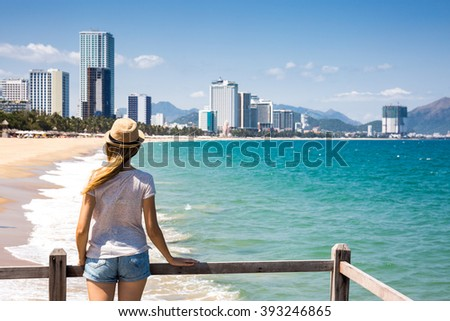 Female tourist watching waves, urban background