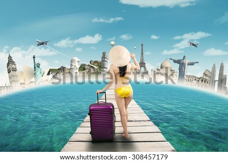 Female tourist wearing bikini and standing on the bridge while carrying bag to vacation on the worldwide monuments - stock photo