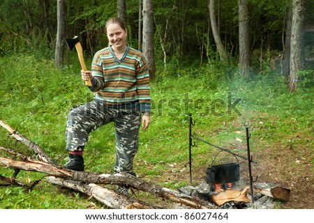 Female tourist with axe making firewoods - stock photo
