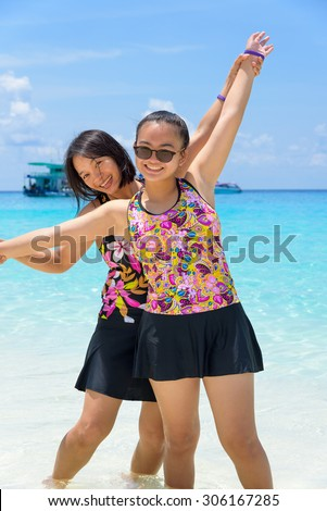 Female tourists mother and daughter in swimsuits smiling happily on the beach at Koh Miang island is a beautiful attractions famous of sea in Mu Ko Similan National Park, Phang Nga Province, Thailand - stock photo