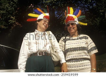 Female tourists with Indian headdresses looking over Hawks Nest State Park Overlook on Scenic Highway US Route 60 on New River, Ansted, WV - stock photo