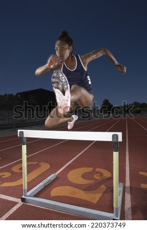 Female track athlete clears a hurdle - stock photo