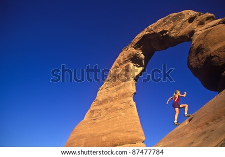 Female trail runner jogs under The Delicate Arch. - stock photo