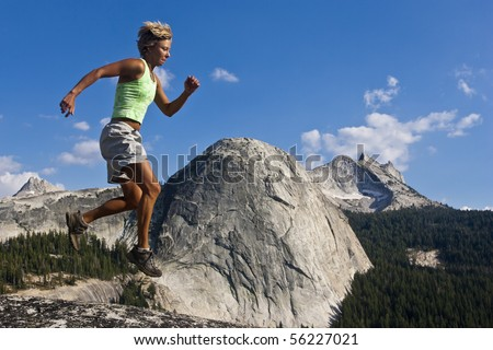 Female trail runner leaps an obstacle along a mountain top.