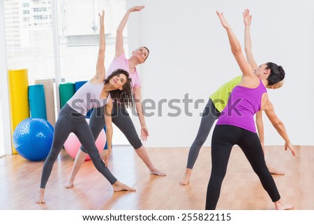 Female trainer and female friends doing stretching exercise at gym
