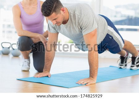 Female trainer assisting man with push ups at gym - stock photo