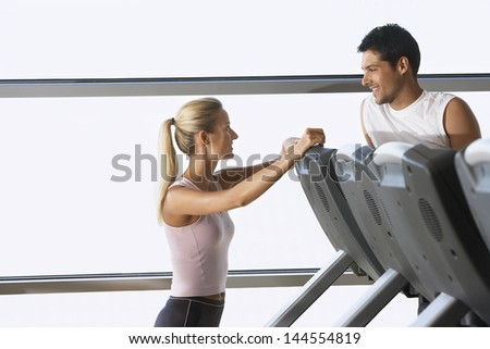 Female trainer conversing with man on treadmill at gym