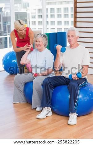 Female trainer motivating senior couple in lifting dumbbells at gym - stock photo