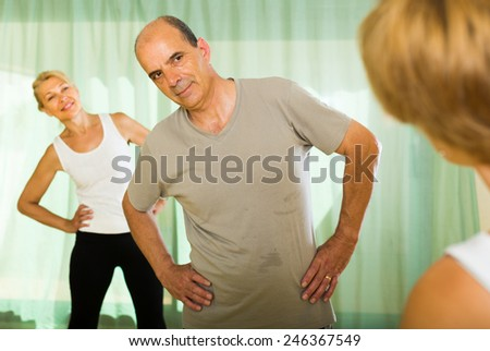 Female trainer showing positive elderly couple how to incline the body  - stock photo