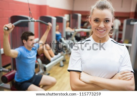Female trainer smiling in front of class in weights room in gym - stock photo