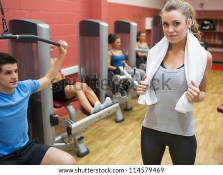 Female trainer teaching her fitness class in weights room in gym - stock photo