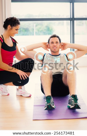Female trainer watching man do abdominal crunches on exercise mat against fitness interface - stock photo