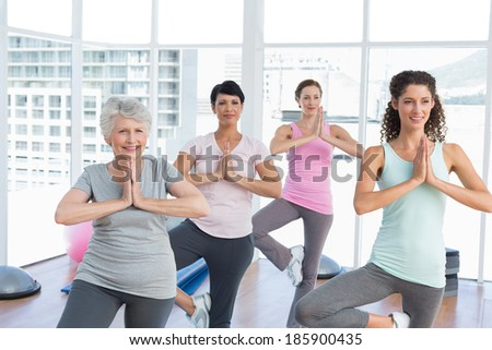 Female trainer with class standing in namaste pose at yoga class - stock photo