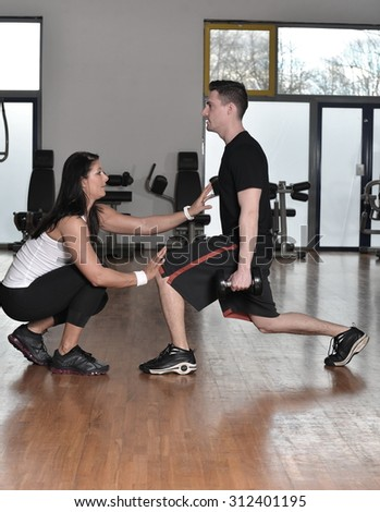 Female trainer working with her trainee with weight training equipment