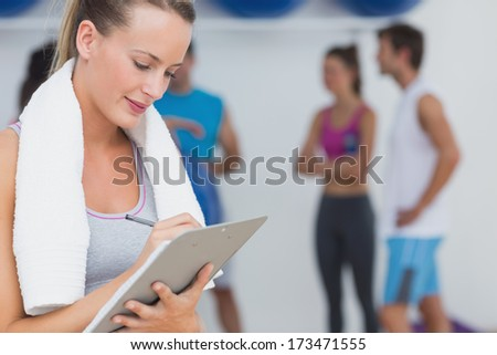Female trainer writing on clipboard with fitness class in background at the gym