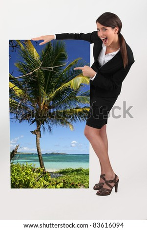 female travel agent showing poster of tropical beach - stock photo