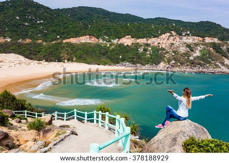 Female traveler sitting on rock with outspread hands, enjoying view on beach and waves