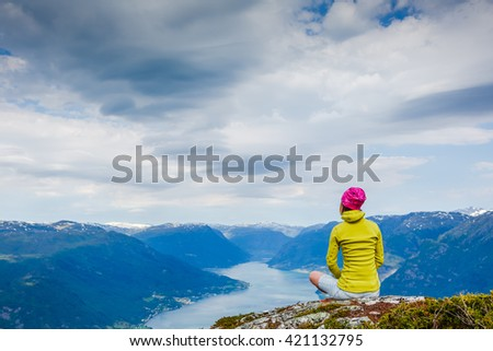 Female traveler takes rest on top of mountain in Norway - stock photo