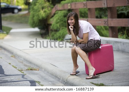 female traveler waiting with her suitcase