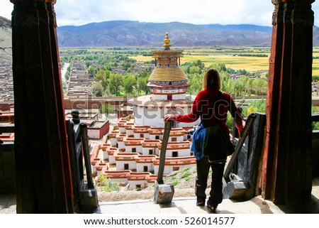 Female traveller standing on top of stairs of a monastery looking at the Buddhist Kumbum chorten in Gyantse town, in the Tibet Autonomous Region of China.