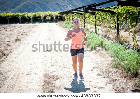 Female triathlete running on a trail on a bright sunny day in the vineyards of the Western Cape of South Africa