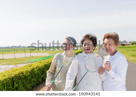 Female trio that pose happily with a racket