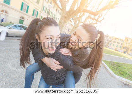 Female Twins Playing together and Enjoy Getting Piggyback Ride. They are Smiling and Looking Each Other. They wear Similar Clothes and they both Have Ponytail Hair. - stock photo