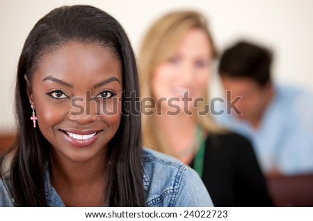 female university student in a classroom smiling