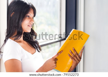 female university student reading book by the window - stock photo