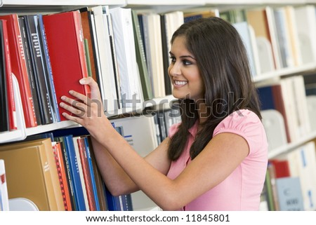 Female university student selecting book from library shelf - stock photo