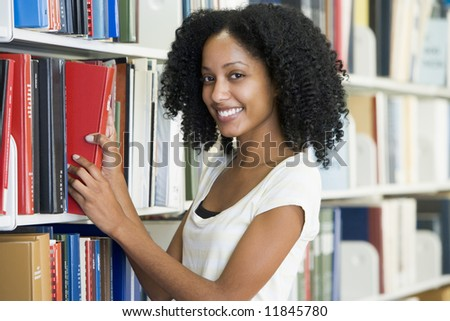 Female university student selecting library book from shelf - stock photo