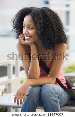 Female university student sitting outside - stock photo