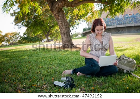 Female university student working on a laptop in green park