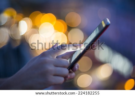 Female using her mobile phone, city skyline night light  background - stock photo