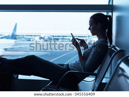Female using her smart phone at the airport.  - stock photo