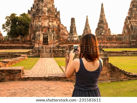 female using smart-phone at sight seeing place  in Thailand ancient temple - stock photo