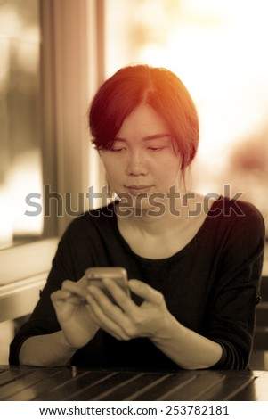 Female using smartphone in cafe. Vintage filter. - stock photo
