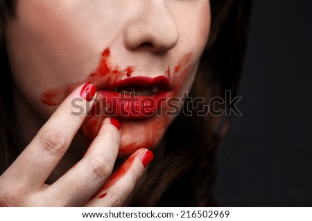 Female vampire with bloody moutgh after biting someone