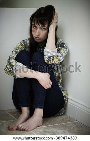 Female Victim Of Domestic Abuse Sitting On Floor - stock photo